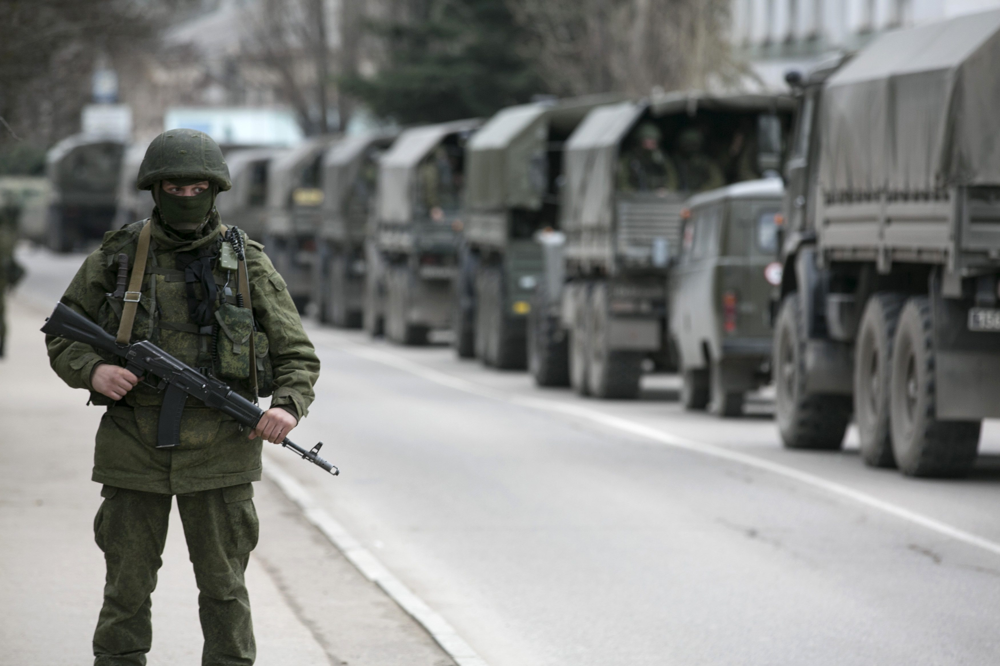 An armed serviceman stands near Russian army vehicles outside a Ukrainian border guard post in the Crimean town of Balaclava